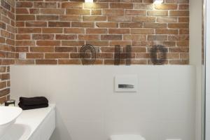 Biała łazienka z cegłą – gotowy projekt w stylu loft