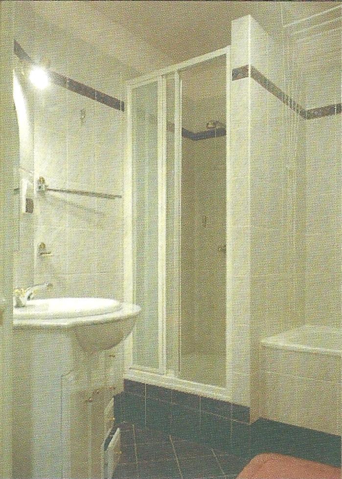 Łazienka w typowym domu wielorodzinnym. Przed przebudowę było tu miejsce jedynie na matą umywalkę, wannę i pralkę. Powiększenie łazienki kosztem przedpokoju pozwoliło na wstawienie kabiny prysznicowej (z drzwiami ze stali hartowanej, no stalowych prowadnicach) i dużej umywalki osadzonej w blacie z sza/fcj. Łazienka jest utrzymana w różowo-bordowej tonacji, wykorzystano najtańszą glazurę i terakotę. Nad lustrem - dwa kinkiety na zwykłe żarówki.