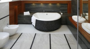 Ciemne kolory ocieplone drewnem: trzy gotowe projekty łazienek