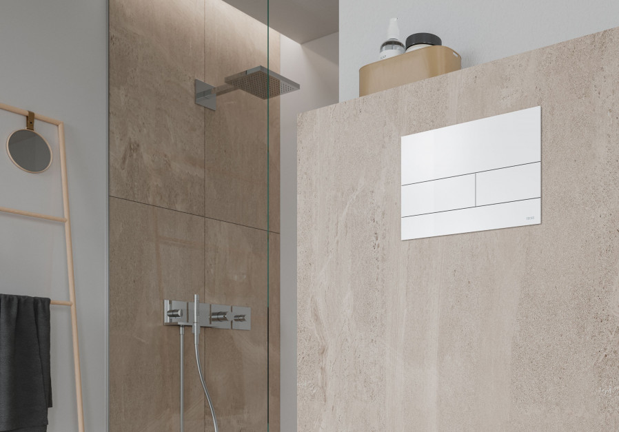 Detal w łazience: matowy przycisk spłukujący w bieli